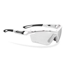 Очки Rudy Project TRALYX WHITE GLOSS - ImpX PHOTO CHR 2BLACKВелоочки<br>ОписаниеОчки Rudy Project TRALYX WHITE GLOSS - ImpX PHOTOCHR 2BLACKПрименениеСпортивные очки для занятия велосипедом, бегом, лыжами, активного отдыха.Tralyx - одна из самых продвинутых и технологичных моделей Rudy Project, способная покорить с первого взгляда. Любимые очки многих профессионалов и любителей спорта вполне заслужили свою репутацию: они сочетают лучшую функциональность с более высокими характеристиками и качеством линз, чем у конкурентов. Аэродинамический дизайн сотверстиями для вентиляции создан на основе научных исследований и обеспечивает оптимальную циркуляцию воздуха для предотвращения запотевания очков.Профиль выполнен таким образом, что потоки нагнетаемого воздуха не мешают зрению. Глаза надёжно защищены от попадания пыли, песка, брызг и любого крупного мусора за счёт прочного матерала оправы идеформируемых линз, не образующих осколков даже при сильном повреждении.ТехнологииADJUSTABLE NOSE PIECEРегулируемый наносник позволяет изменить посадку и добиться максимального комфорта.ADJUSTABLE TEMPLESРегулируемые заушины для лучшей фиксации очков вне зависимости от формы головы.GRILAMID FRAMEДля особой долговечности рамка очков изготовлена из Grilamid® - это лёгкий ударопрочный гипоаллергенный высококачественный термопласт стабильный при длительном использовании и перепадах температуры.QUICK CHANGE SYSTEMСистема Quick Change позволяет осуществлять быструю замену линз разного типа и размера. Это обеспечивает наибольшую функциональность и идеальные условия для зрения при любых погодных условиях.LENS SHAPESШирокий диапазон регулировок для подгонки посадки всегда был отличительным качеством продукции Rudy Project. Новые линзы размеров SX и XL - ясное подтверждениеэффективной работы в заданном направлении. Размер соответствует форме лица и обеспечивает оптимальные условия и защиту для глаз.POWERFLOWНовая система PowerFlow обеспечивает беспрецедентную терморегуляцию благодаря научному под